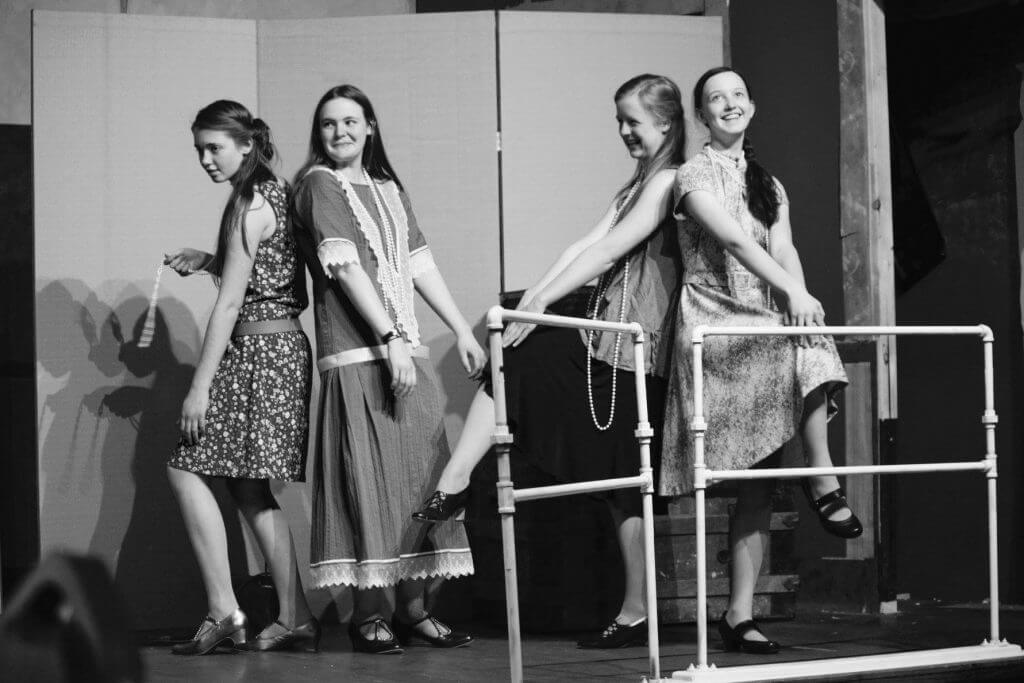 girls acting as flappers pose onstage