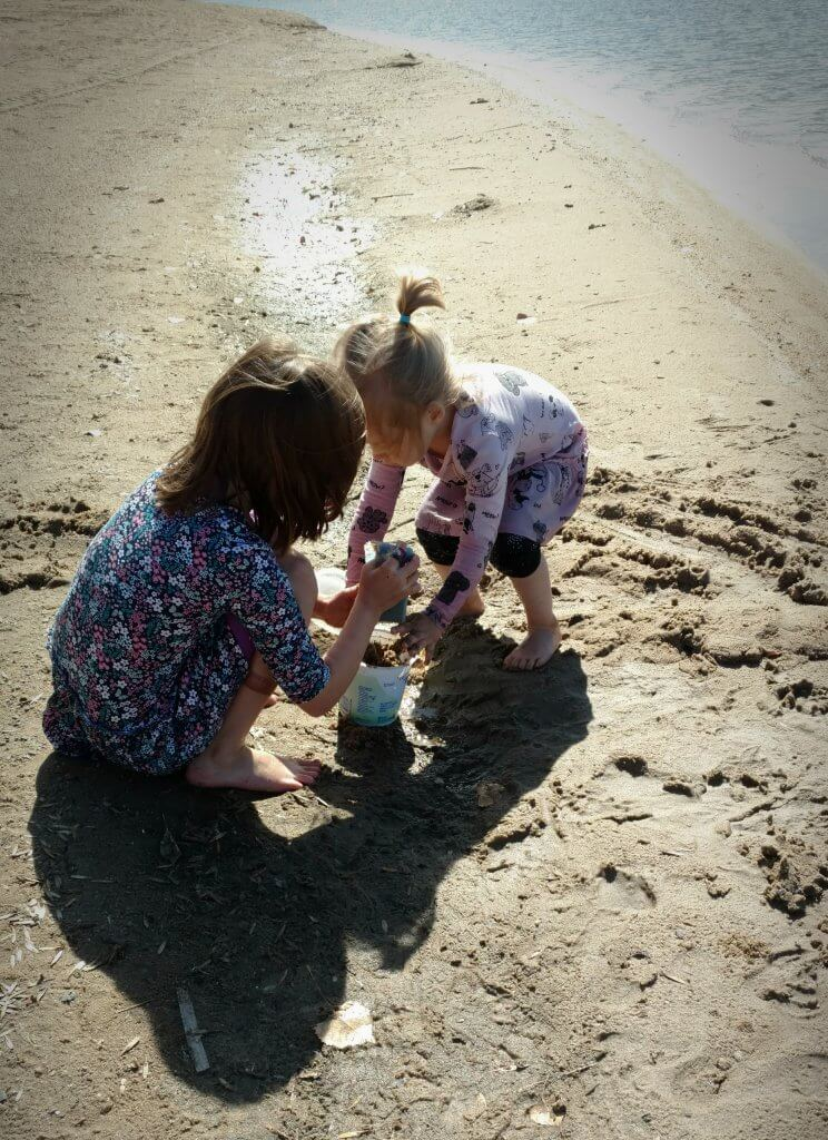 two little girls playing on a sandy beach
