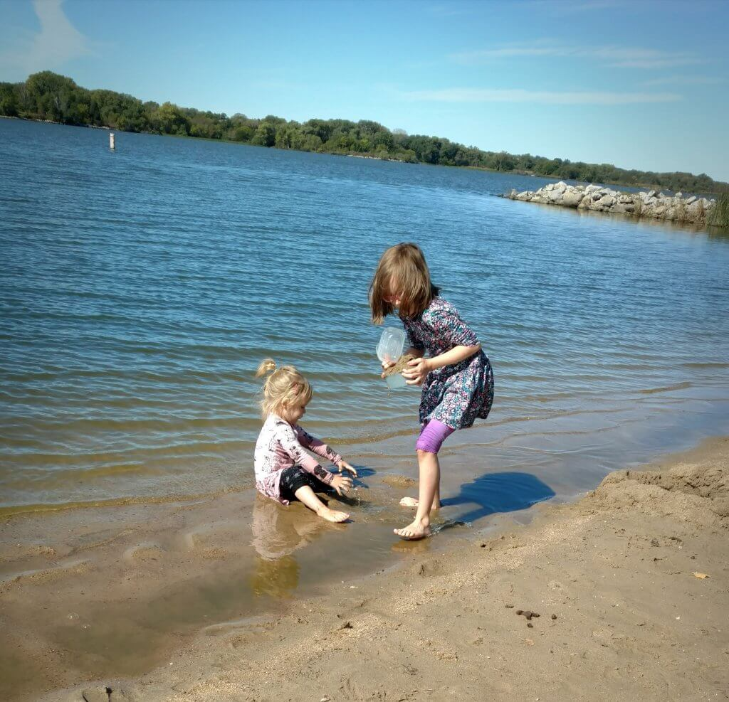 two little girls playing in the lake water