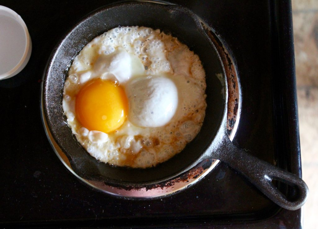 The egg begins to fry . . . but then you add water and a lid . . .