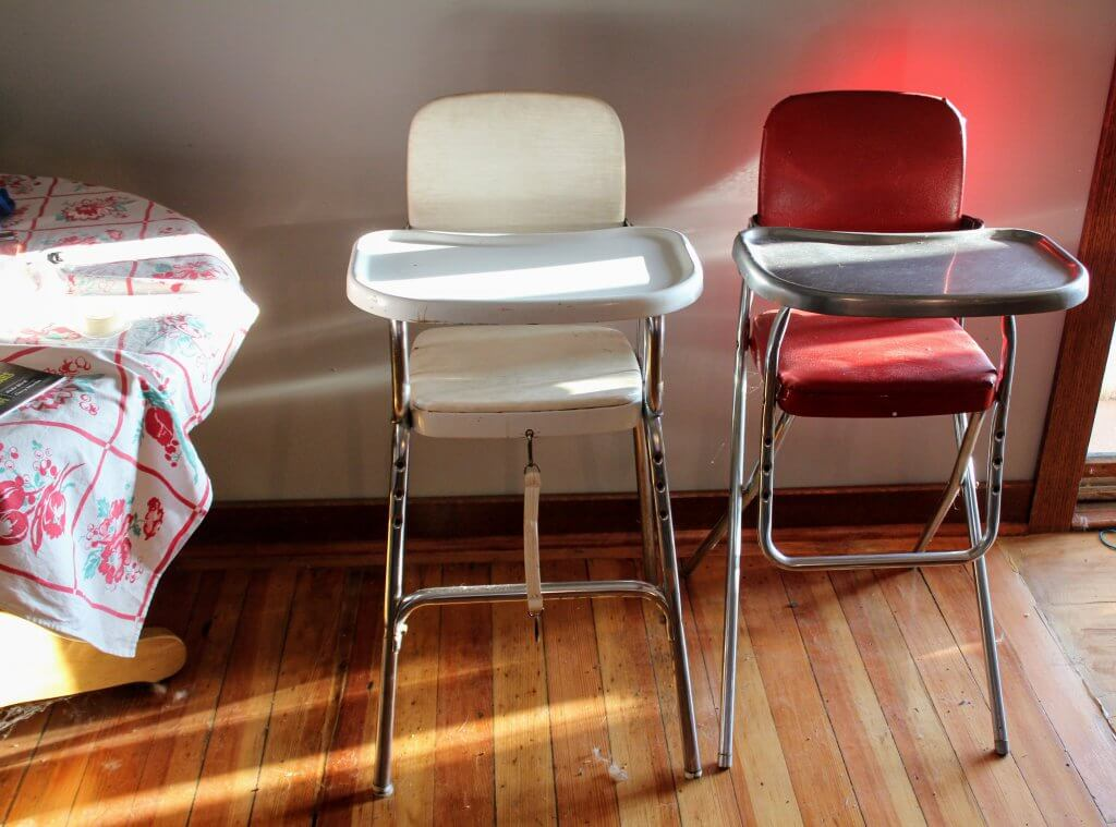 two old high chairs, wooden floor, sunshine