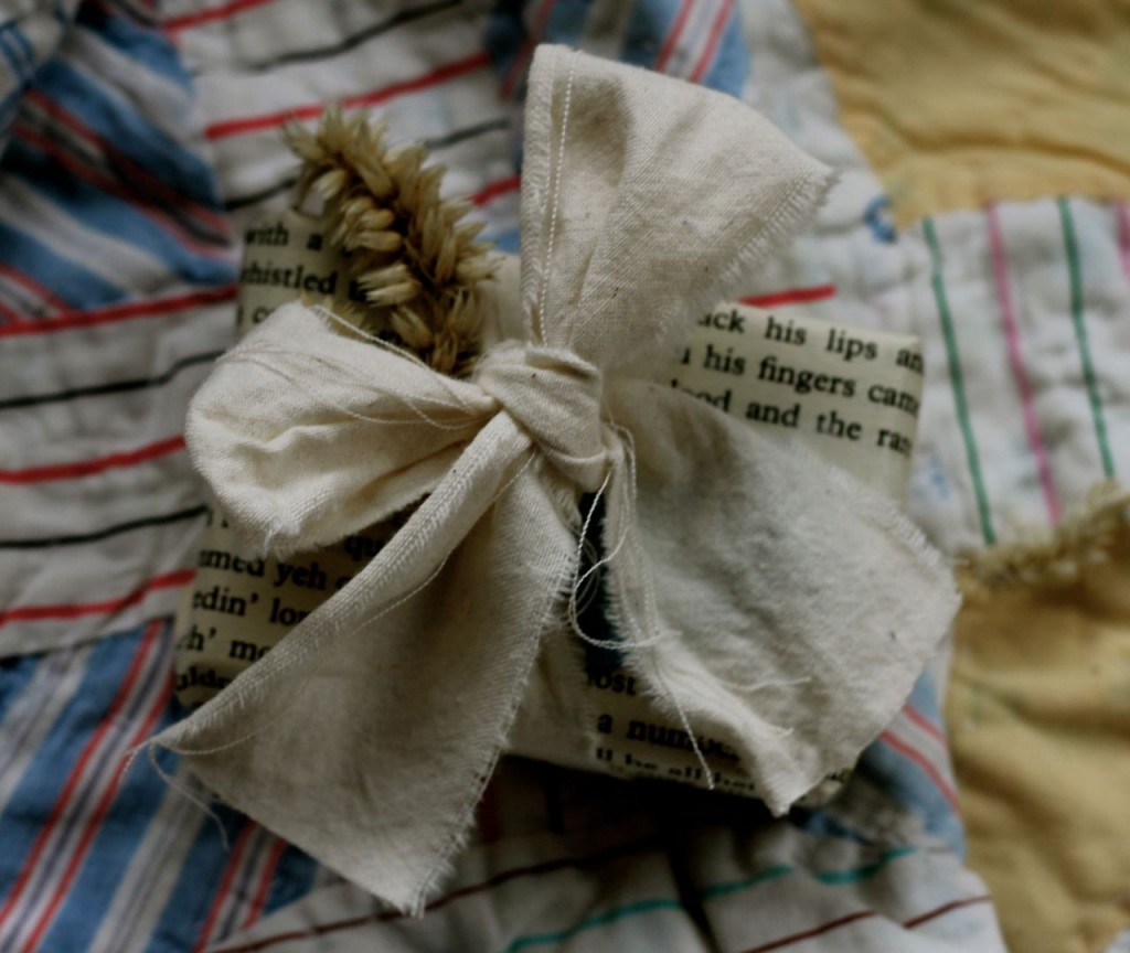 Little bitty package, big bow made of muslin, dried flower and book page.