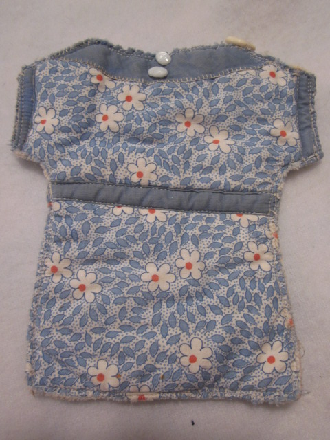 Isn't this sweet?  I especially like the tiny miniature buttons and the hand-stitching around the yoke of the dress.