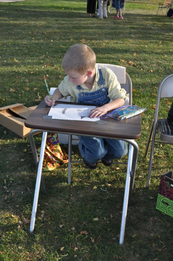 This is a much safer place for my son to draw: outside, with a pile of clean white paper, plenty of grass, and trees. No tempting blank walls.
