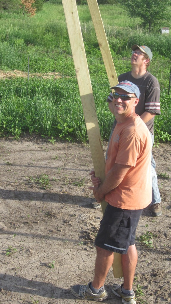 Bryan and Dave grab boards to prop up the purlin so Timothy can install it.