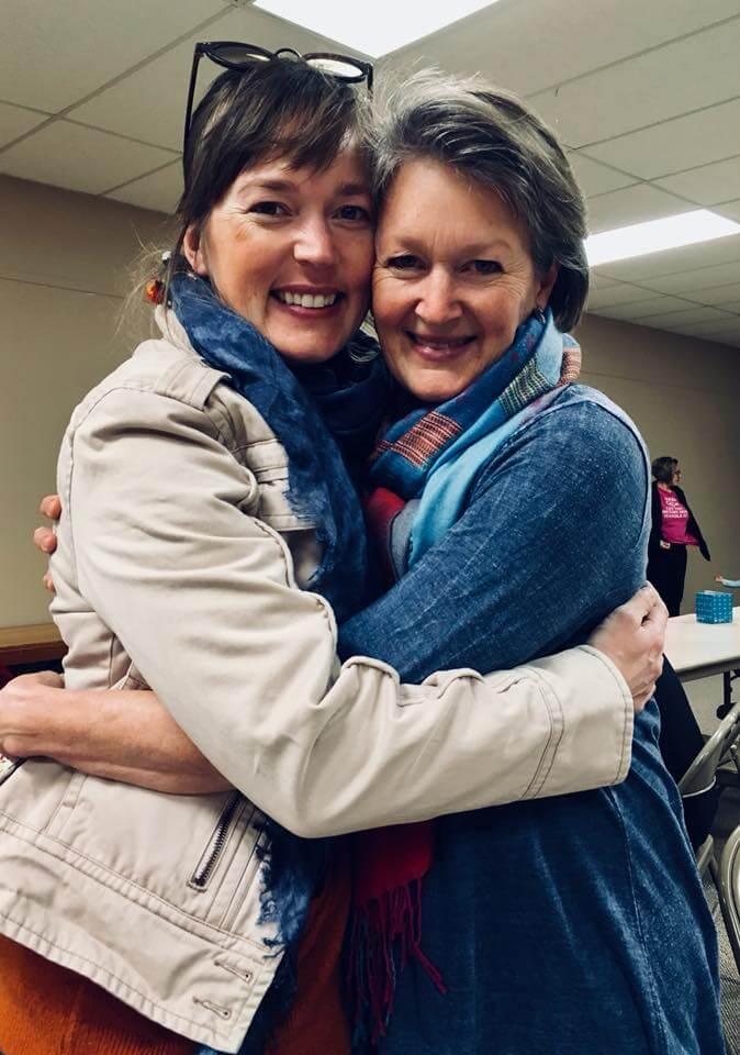 two ladies embracing, smiling