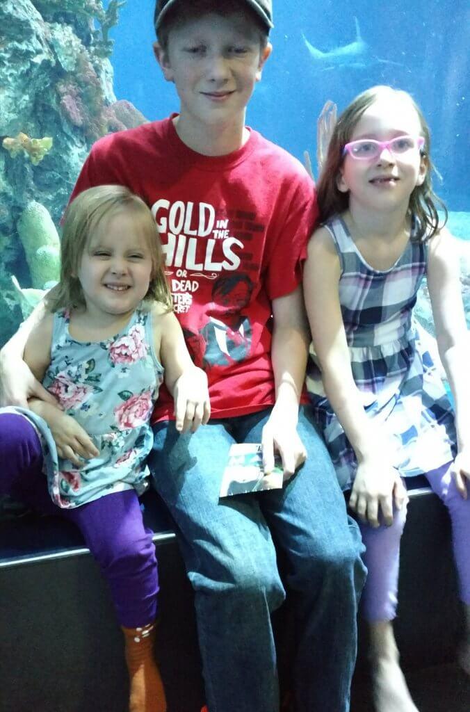 three children at zoo aquarium