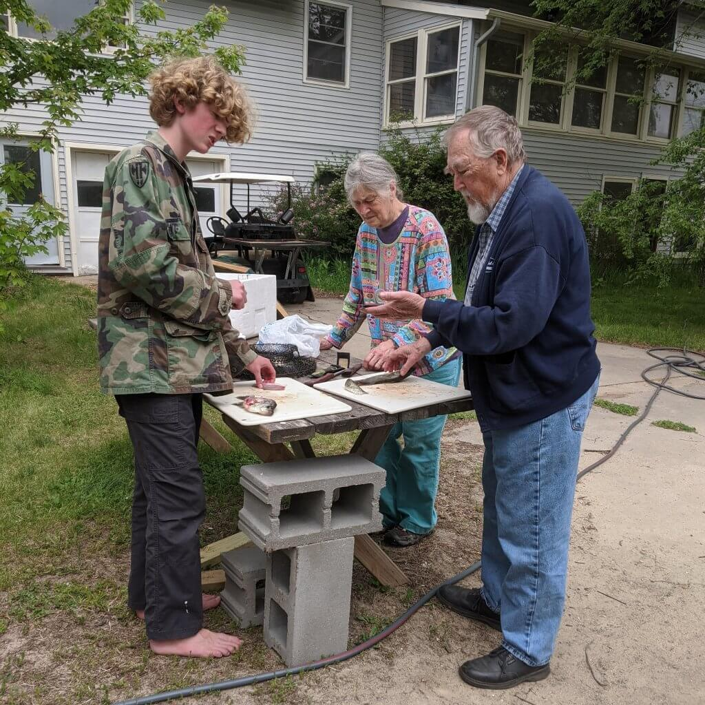 boy with grandparents, gutting fish