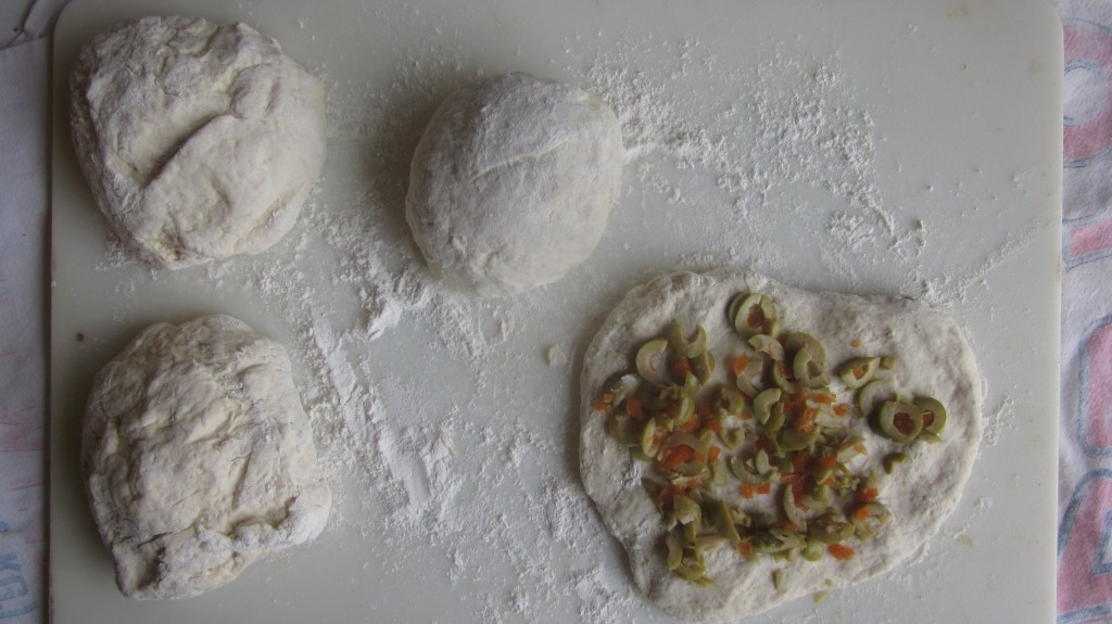 From the recipe, I've split the dough into four balls, one of which is rolled out flat and olives spread on it. The middle ball is ready to rise, and the two on the left are not formed yet.