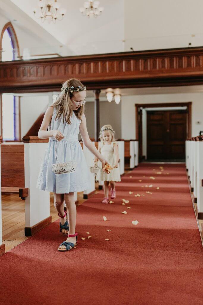 two flower girls scattering petals in chapel