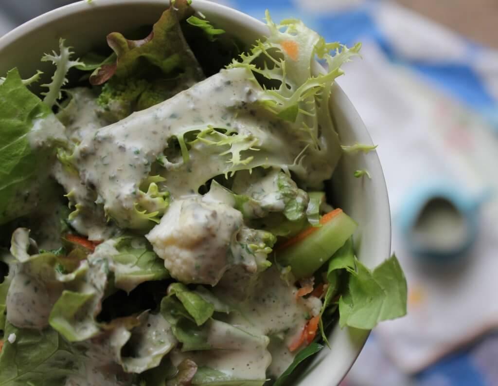 creamy salad dressing on bowlful of greens