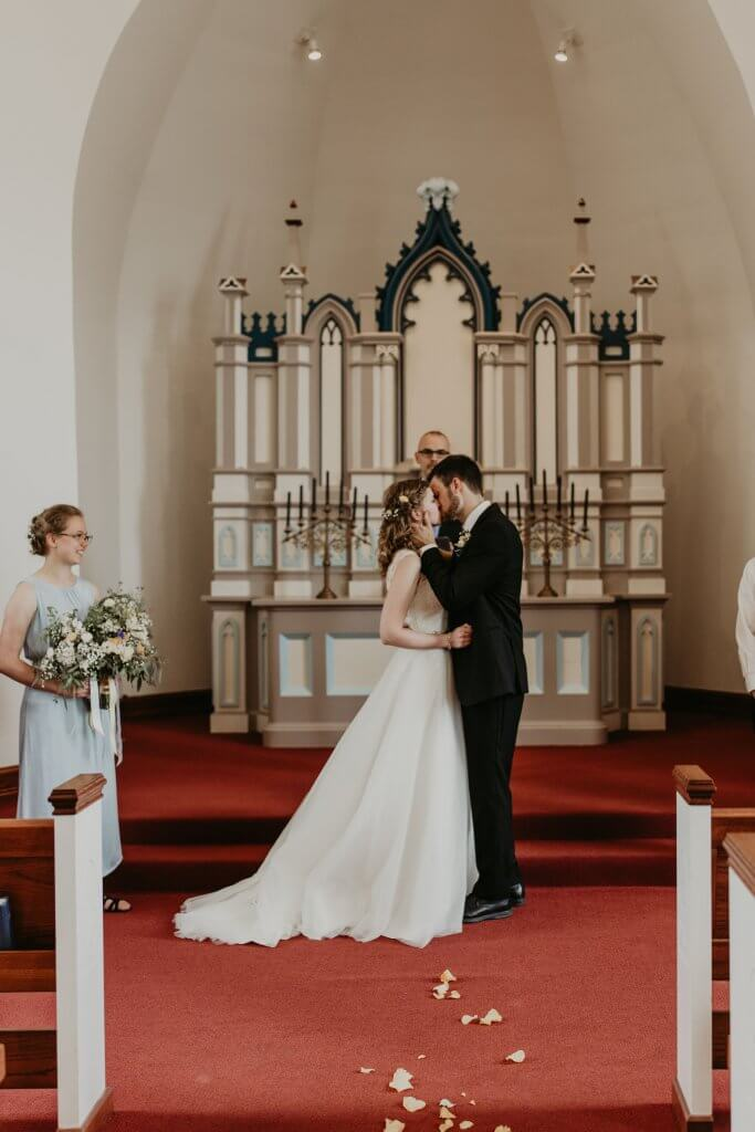 bride & groom kissing in chapel