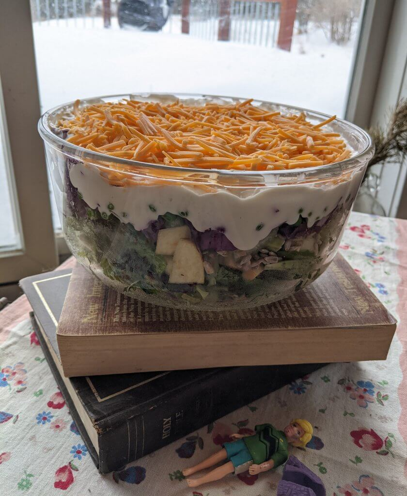 bowl of salad on top some books