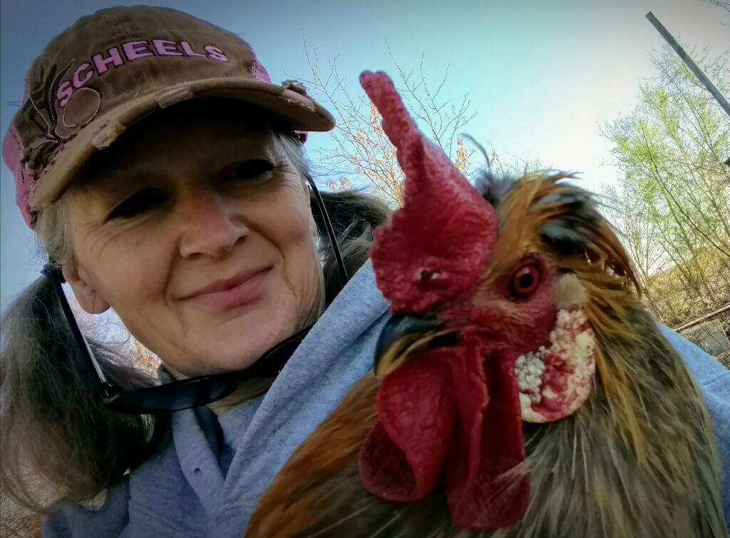 Woman with hat, holding rooster.