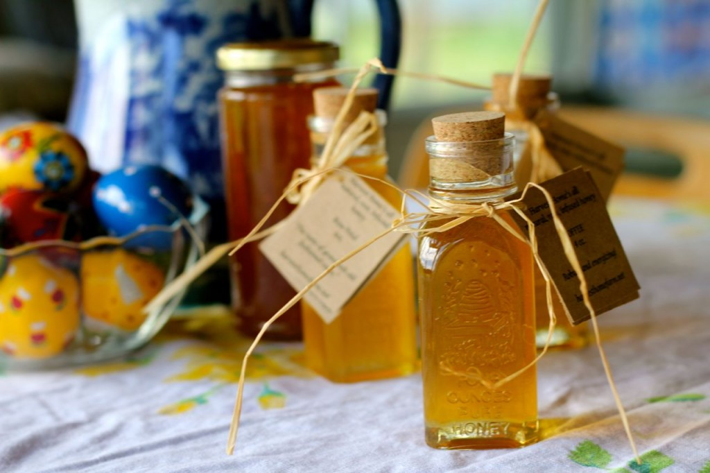 Four bottles of honey: clover honey from our farm, and three jars of infused honey from Harvest Home Farm.