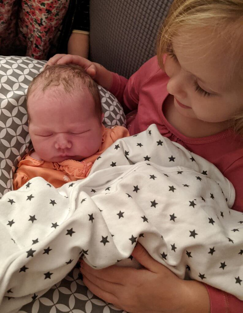 little girl holding new baby