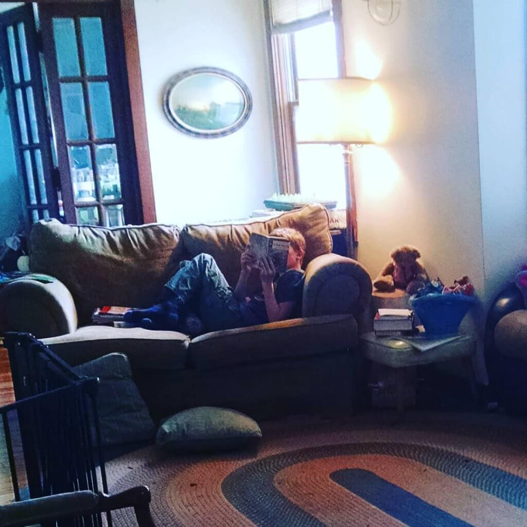 boy reading book in living room