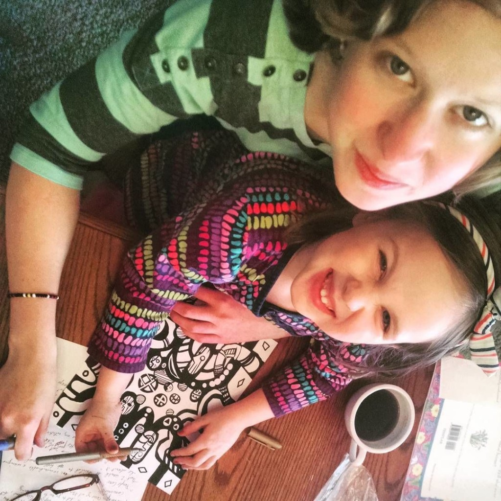 young lady and child coloring together
